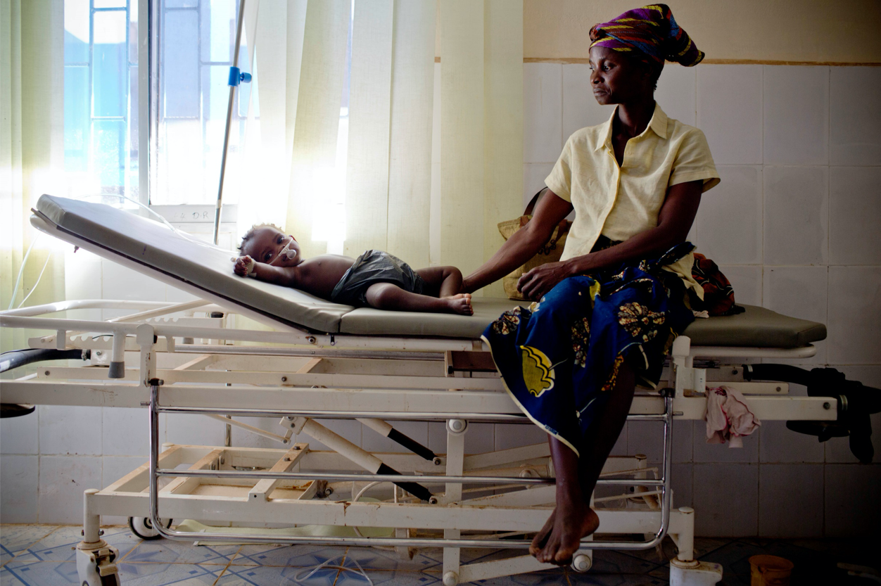 Photo of a woman with a baby on a hospital bed.