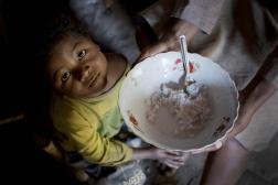 Photo of a young girl looking up at a bowl of porridge.