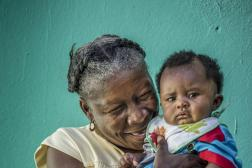 Haitian woman holding toddler in front of green backdrop.